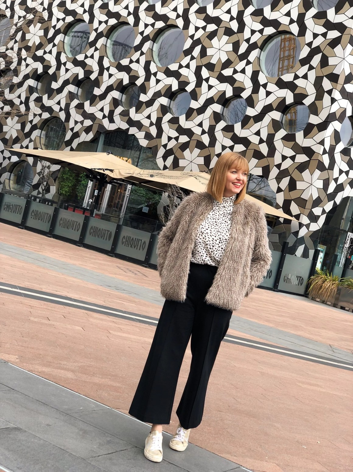 Snow leopard top, black ponte trousers, gold trainers and faux fur jacket