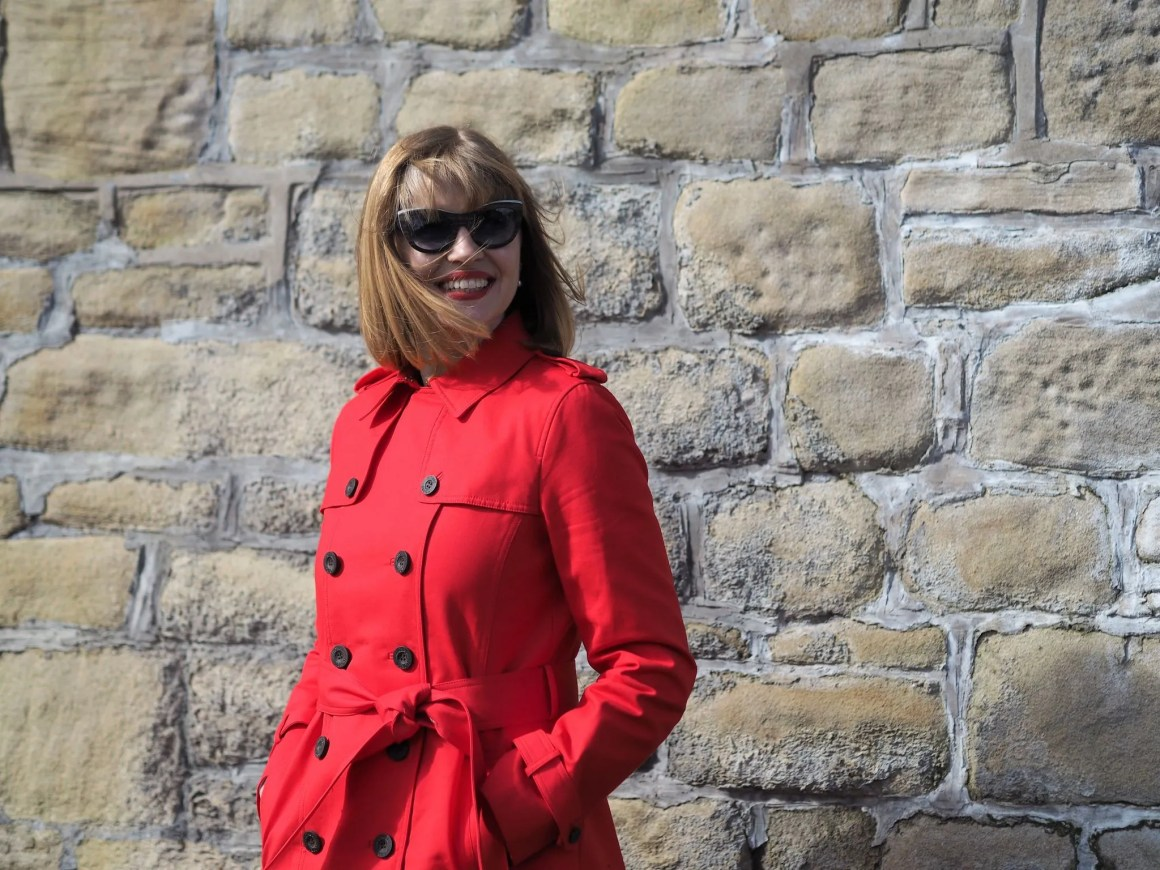 red trench coat and wooden cats eye sunglasses