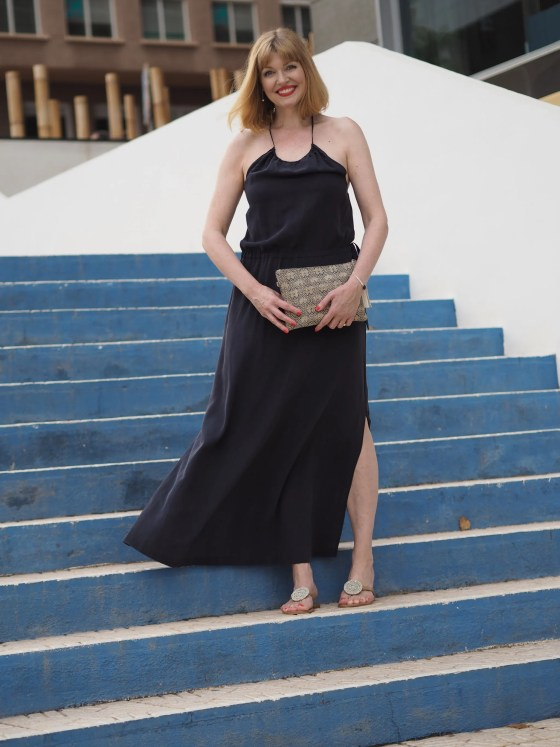 Navy silk halterneck dress and navy raffia clutch bag