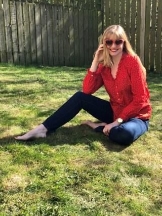 woman wearing red spotted top and red heart sunglasses sitting in sunshine