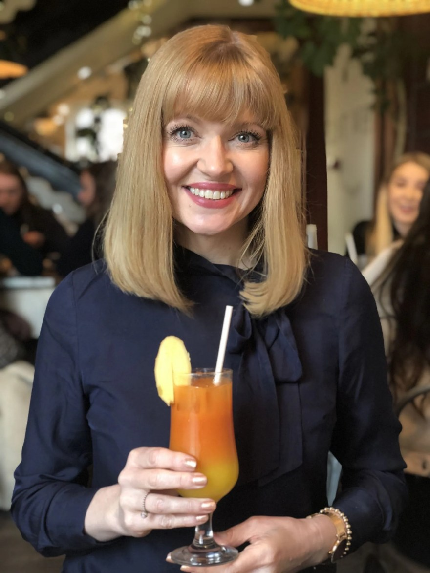 woman drinking orange, ginger and carrot juice coktail