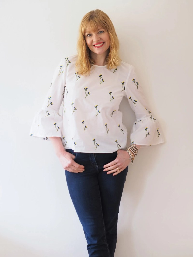 woman wearing white embroidered blouse and jeans