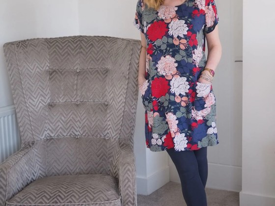 woman standing by chair wearing floral tunic and leggings