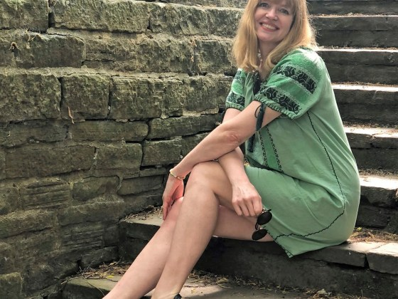 woman sitting on steps wearing green embroidered dress