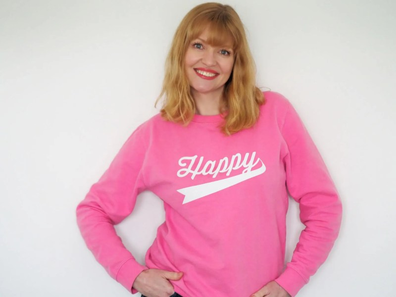 woman smiling wearing pink happy sweatshirt