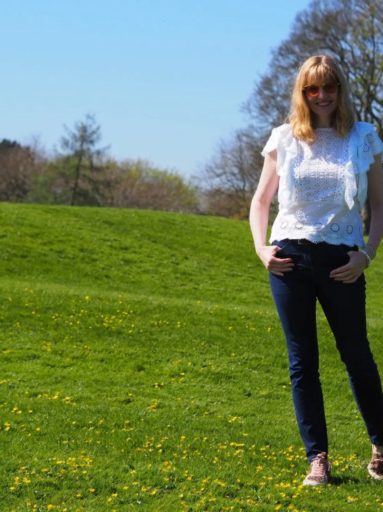 woman wearing broderie anglaise top standing in sunshine