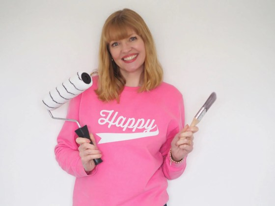 woman wearing happy sweatshirt amd holding paintbrush