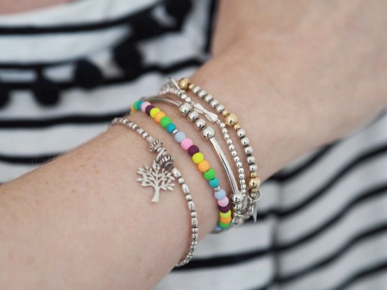 Stack of silver bracalets with NHS rainbow bracelet