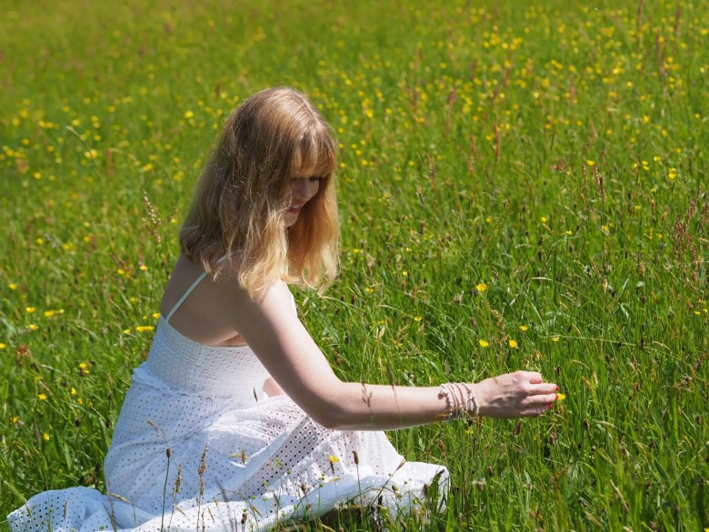 woman in wildflower meadow wearing white broderie anglaise maxi dress and white bracelets