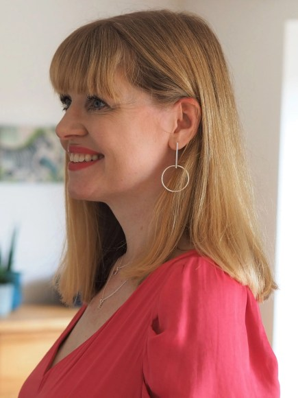 woman wearing silver drop earrings