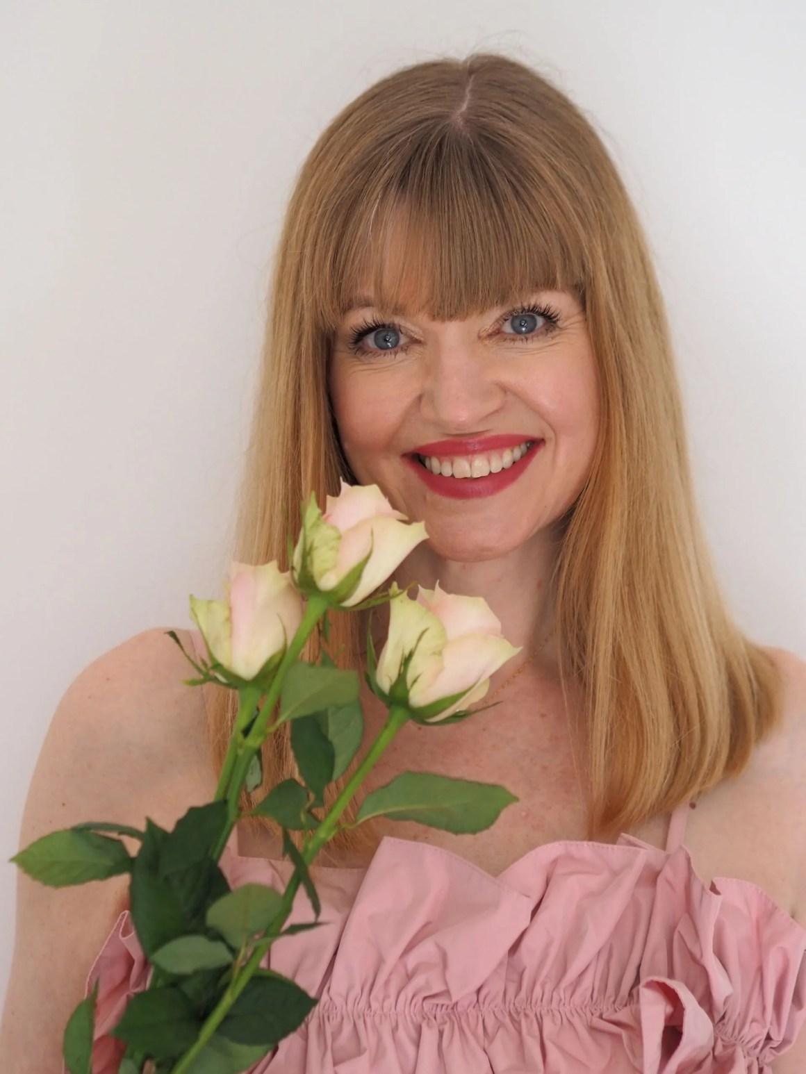 woman wearing blush pink dress holding pale roses