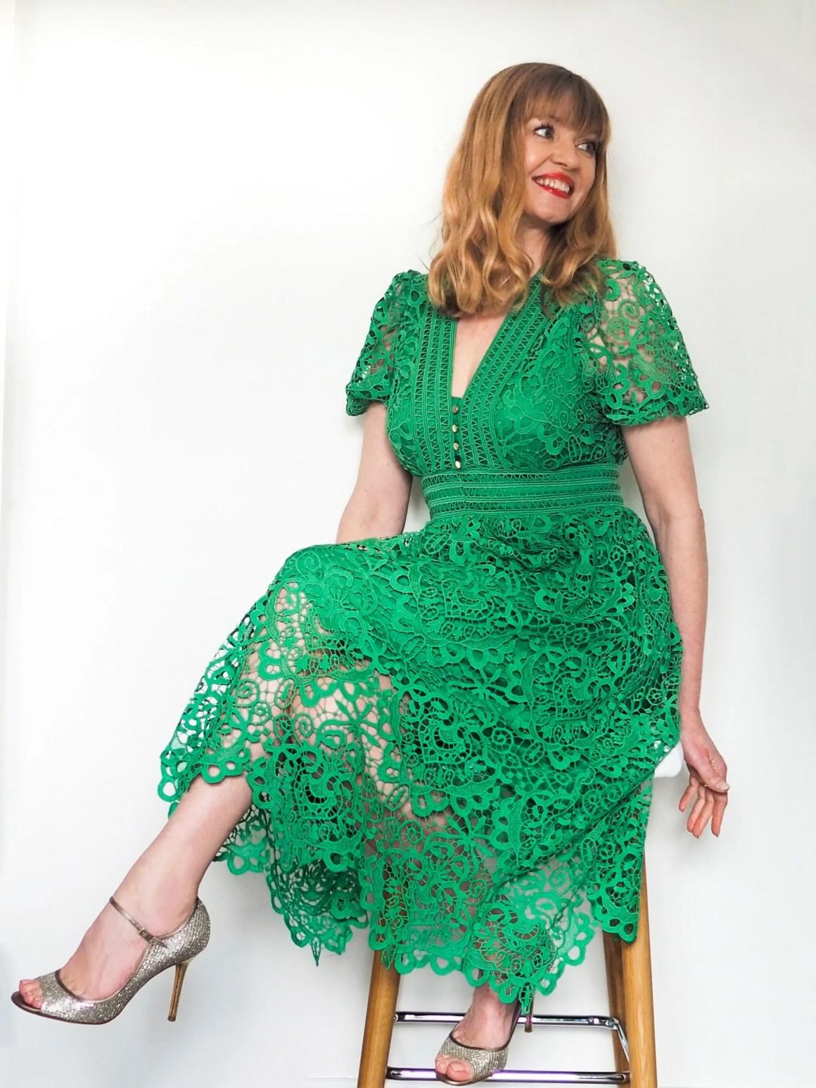 Elizabeth wears green cut-work lace midi dress
