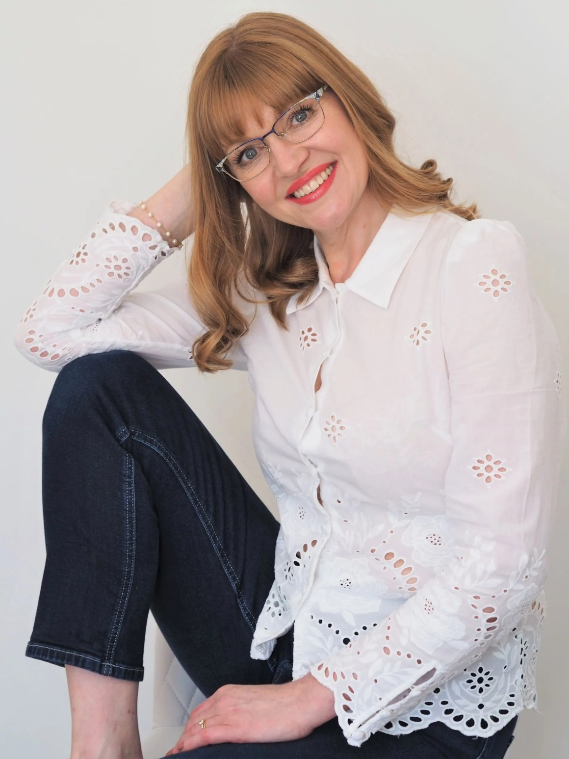 woman wears grey titanium eyewear with white eyelet blouse and denim jeans