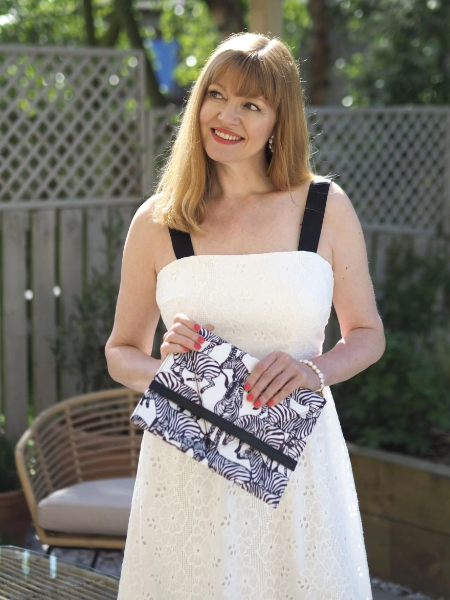 white broderie maxi with black strap detail with zebra print clutch bag
