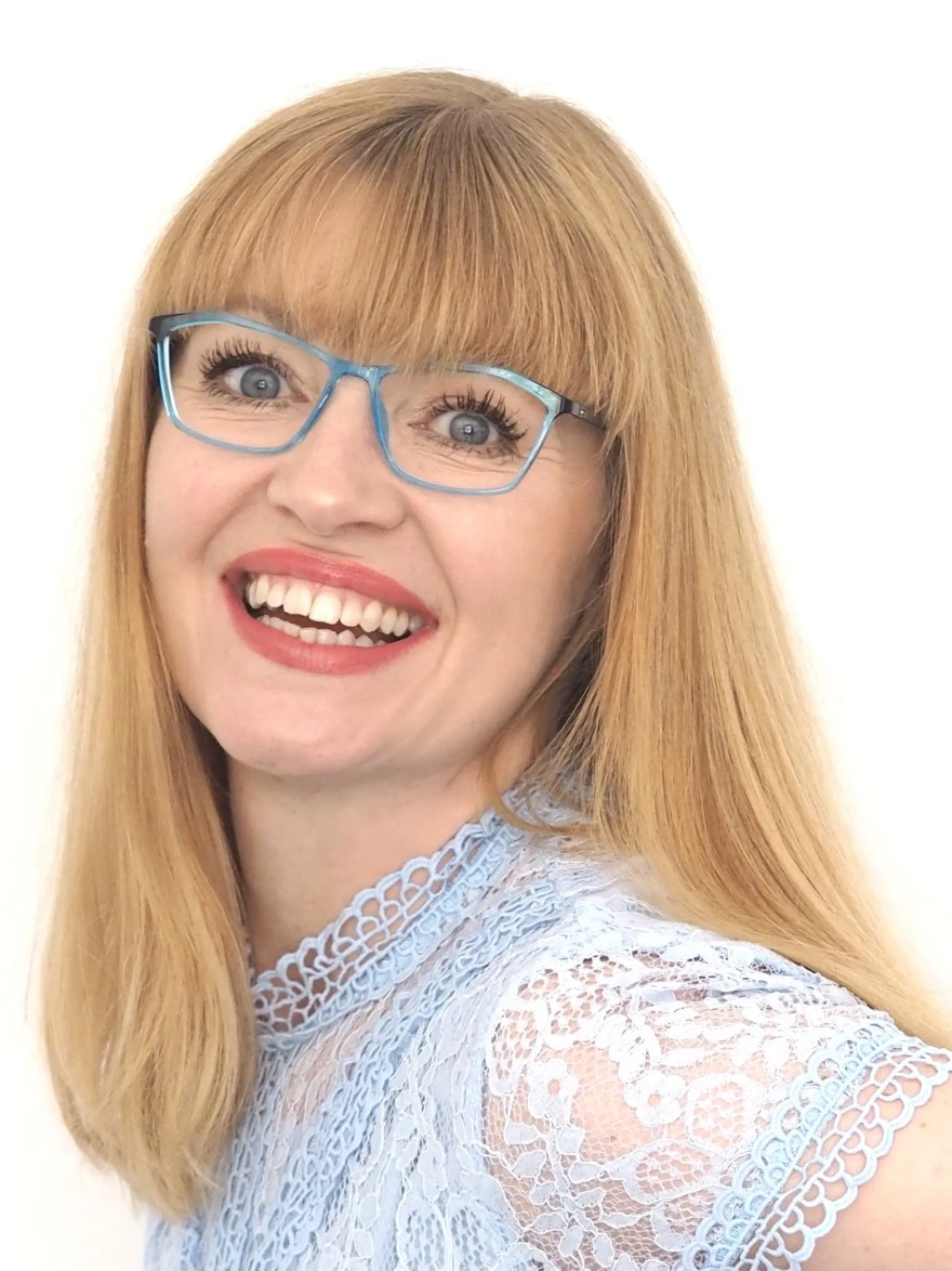 woman wears pale blue eyewear and pale blue lace dress