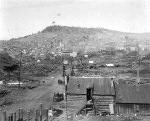 A view of the smoking remains of the town, a few buildings standing among the wreckage of dozens.