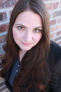 Rachel Robison Greene looks at the camera. She is a woman with light skin, long dark brown hair, and brown eyes. She wears a black blazer and grey blouse and stands in front of a brick wall.