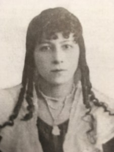 A woman with long dark ringlets and a high collared dress and shawl stares pensively at the camera