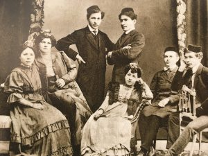 A group of people wearing early 20th century clothes stands and sits, staring at the camera.