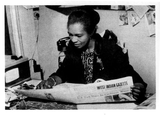 """A well-dressed Black woman with her hair pulled back into a bun sits at a desk covered with newsprint, reading a copy of a newspaper titled """"West Indian Gazette."""""""