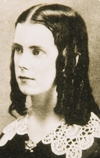 A young girl with dark ringlets and a lace collar is shown in near-profile