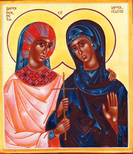 A painting shows two dark-skinned women dressed in robes (red and pink for Perpetua, blues for Felicitas) with their arms around one another and both holding a gold cross. Their haloes are intertwined behind them.