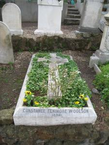 A stone or cement cross lies surrounded with flowers and greenery in a stone or cement rectangular grave cover, inscribed with Woolson's name
