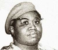 An African American woman stares directly at the camera with a serious expression. She is wearing a beret, glasses and a high-collared shirt,