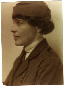 A white woman in a military-style coat, skirt and hat is seen in profile facing left. She has short dark hair and light eyes.