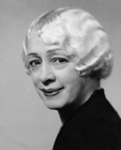 A middle-aged woman with white hair and dark eyes smiles at an angle at the viewer. She is attractive and striking in a high collared black blouse and dark lipstick.
