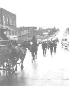 A group of people in black clothing walk in front of a black stallion and a horse and cart bearing a coffin down the main street of Cripple Creek, Colorado.