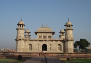 A white marble building with four towers, a central raised section and broad entry path.
