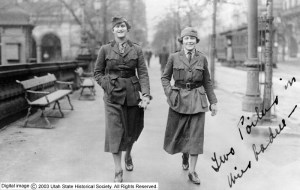 Two women in WWI uniform stride toward the viewer, hands in pockets, broad confident smiles on their faces.