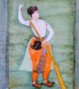 Nur Jahan shown dressed in man's clothing of 17th century India (full orange trousers and white shirt, wtih black turban) and holding a rifle with her hand on the muzzle.