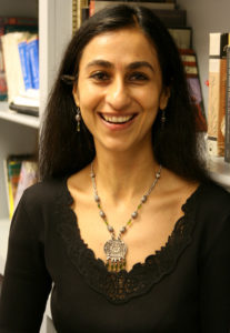 Dr Ruby Lal smiles at the camera. She has dark hair, and is wearing a brown shirt and large silver pendant necklace.