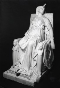 A marble statue of a woman in a draped robe, leaned back in a throne in an expression of distress