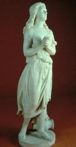A marble statue in Neo-Classical style of a woman weraing a draped robe and standing with clasped hands