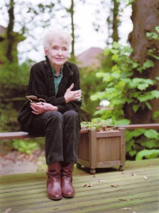 An elderly woman sits on a wood slat in a garden next to a planter box. She wears dark trousers and jacket, and brown boots. She sits leaning foward with her arms crossed over her body staring past the camera with a pleasant expression.