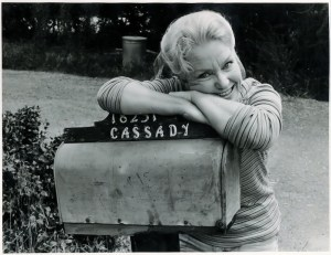 """A middle-aged woman leans her face on her arms on top of a mailbox which reads """"Cassady."""" She smiles happily at the camera."""
