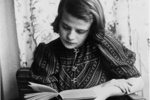 A young woman reads a book. She wears a patterned blouse with metal clasp closures and her hair is loose to her shoulders.