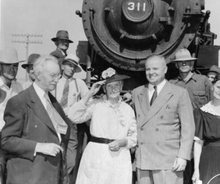 An elderly woman in a white dress and black hat stands smiling between two men in suits and in front of a train engine.