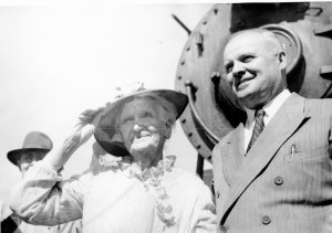 An elderly white woman in white dress and black hat stands next to a man in a suit in front of a train engine.