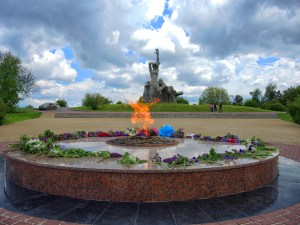 A round stone table monument with a flame at the center is ringed with greenery and flowers in front of a statue of larger-than-life human figures