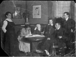 A group of adults in turn of the century European dress sit around a table, seemingly in discussion.
