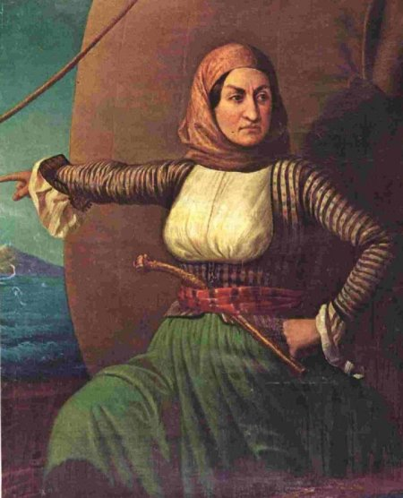 Bouboulina stands on her ship, pointing into the distance. She wears a pirate-looking outfit with pistol thrust through her waistband and a determined expression.