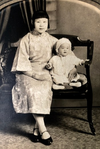 A Chinese American woman and baby sit on a formal bench dressed in light colored formal clothing