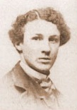 Joseph Jacobs. A young man with curly dark hair and light skin wearing 19th century suit and cravat, etc, looks pensively at the camera.
