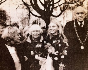 Two older women and one young woman hold a wreath and smile at one another, standing alongside a man in formal ceremonial dress