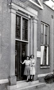 Two teenage girls stand in front of a brick building with a large double door, smiling at the camera. Truus and Freddie Oversteegen, Haarlem.