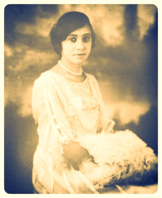 Florence Price as a young woman. A beautiful young woman with light skin and dark hair, wearing a white dress and holding a white fur muff, smiles at the camera.